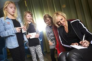 Bildtext 5: Sanna Nielsen skriver autografer åt fans dagen efter schlagersegern. Vilma, Tilde och Tea ber om den stora idolens autograf.