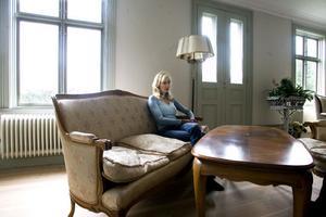 Väggen bakom Kristin Eriksson hade förut de stora skyltfönstren som öppnades för första gången redan år 1926. Nu är de borta, och nya fönster är på plats. Nytillverkade bågar, men gammalt, munblåst glas.