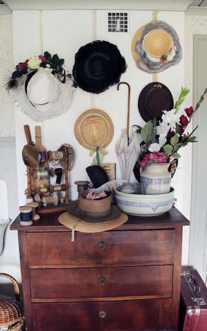 På väggen hänger hattar från olika årtionden.