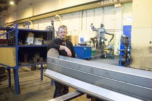 Mikael Birgersson, vd för BGC Plåt, visar en stor rökdetektor som företaget färdigställer.