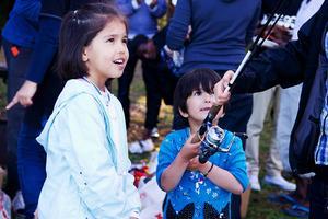 Barnen Vania och Nazanin tittar nyfiket på kastspöet som någon har tagit med sig.