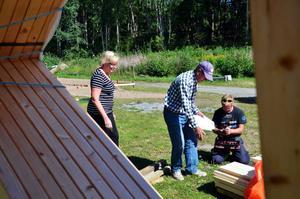 Virke på väg. Sekreteraren Inger Karlsson och byggmästaren Evert Mejstedt tar emot byggmaterial som Hasse Brenden, t höger, levererat.