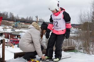 Åttaåriga Delina Stange får hjälp med skidorna innan det är dags att susa nedför backen.