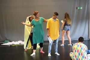 Teaterpedagog Maria Gustafsson visar aktivt hur man använder kroppen på bästa sätt när ungdomarna övar på replikerna.
