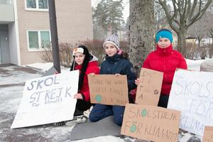 Skoleleverna Frida Vallaste, Tilly Wyatt och Alicia Gustafsson sitter utanför Fagerstas kommunhus för miljöns skull. Greta Thunberg är för dem en stor inspirationskälla och hon finns med på plakaten.