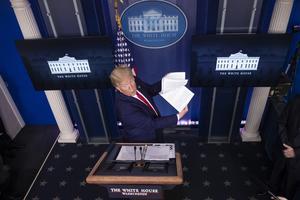 USA:s president Trump bläddrar i en pappersbunt medan han lägger ut texten om coronakrisen. Foto: Alex Brandon/AP