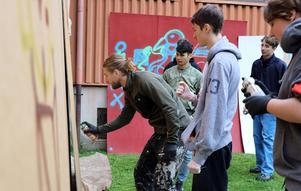 På en bakgård till skolan så fick eleverna själva gå loss och öva med sprayfärgen på uppställda kartongark.