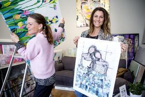 Madeleine Santiago Elofsson visar upp en av sina målningar, medan Linda bringar ordning bland konstverken.