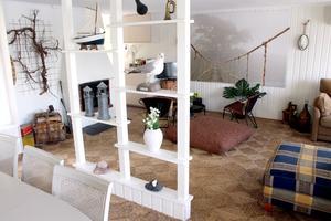 Öppna hyllor som rumsavskiljare och den uppgrävda roten på väggen.