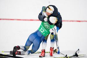 Charlotte Kalla kramar om en utmattad Stina Nilsson efter silvret i damernas sprintstafett. Bild: Petter Arvidson/Bildbyrån.