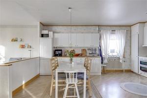 Köket har plats för matbord och stolar och har öppen planlösning mot vardagsrummet. Foto: Fastighetsbyrån.