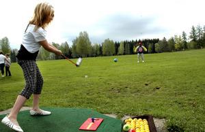 Prickskytte. Wilma Nilsson försöker slå ut golfbollen med kardborreyta i hopp om att i hopp om att den ska fastna på Jörgen Dahlströms specialjacka.