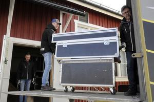 Ola står beredd att ta emot medan Peo och Jan lyfter in. Sammanlagt har de med sig  1500 kilo utrustning bak i bussen.