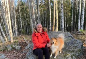 Maria på skogspromenad med hunden Melvin.