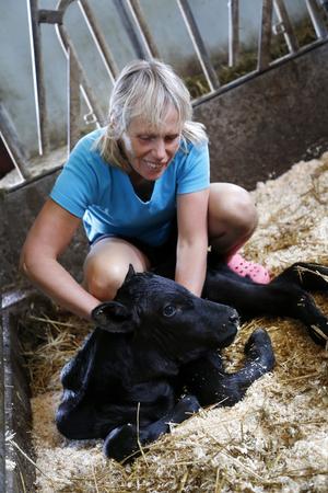 Anita Andersson tittar till den några timmar gamla kalven.