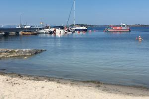Glassbåten kör in mot Nåttarö brygga. Den varma sommaren 2018 krävde frekvent påfyllning i ö-kioskernas frysboxar.