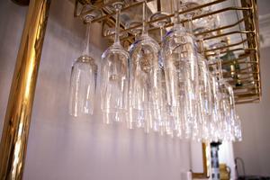 Champagneglasen hänger redo och på hyllan ovanför står champagneflaskorna på rad.