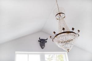 Kristallkrona i nocken i vardagsrummet, och ett tjurhuvud på väggen.