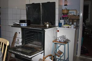Ugnsluckan på den 25 år gamla vedspisen står på vid gavel för att släppa ut värmen i rummet.