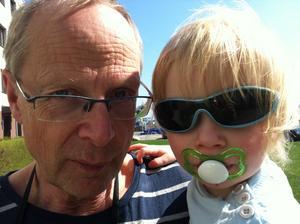 Bilden är tagen en av de första varma dagarna i somras. Barnbarnet Ingrid var lite hängig och vi skulle åka ner på stan, därav nappen. Hon tyckte solen stack i ögonen, därav solglasögonen. När jag höjde kameran för att ta en bild så spexade hon och morfar hängde på. Det blev en kul bild!