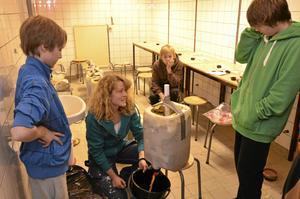 Experiment. Kemisten Lotta Sartz från Bergskraft visar eleverna Matti Väisänen (till vänster), André Forsberg (till höger) och Anton Larsson (i bakgrunden) hur de ska mäta upp vattenmängden i det avfallsprov de jobbar med. BILD: KLAS HOLMQUIST