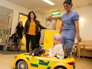 Jaana Naumanen,i svart jacka och gul tröja, förlorade sin dotter Saara i en medfödd och obotlig kärlsjukdom och har nu ordnat en elbil till andra barn som ska till operationssalen. Pengarna kommer från hennes dotter Saaras minnesfond. Till vänster bakom Jaana står Saaras syster Sanna Naumanen. Ellie, 2 år provkör bilen och mormor Louisa Lundström, antestesisjuksköterska på operation, håller koll.