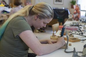 Lotta Leissner bearbetar ett stycke silver som ska bli ett örhänge i form av ett hänglås.
