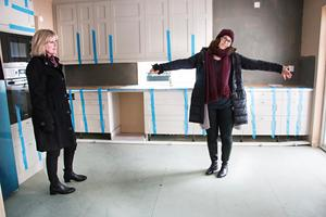 Köksskåpen och mycket av vitvarorna är redan på plats när huset levereras. Malin visar var den blå köksön, som de själva planerar att bygga, ska stå.