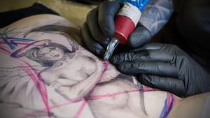 Ängeln växer fram när Anders  Karlsson tatuerar Jannice Frödells rygg.