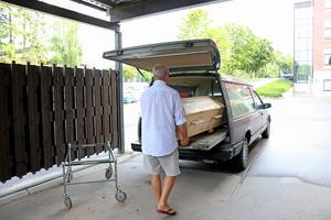 Macke placerar kistan i bilen och kör sedan mot krematoriet där den avlidna personen ska lämnas för kremering.