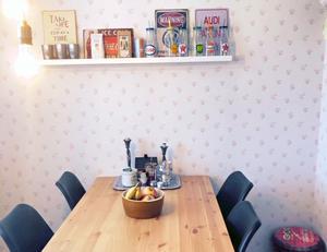Hylla med skyltar och flaskor över köksbordet.
