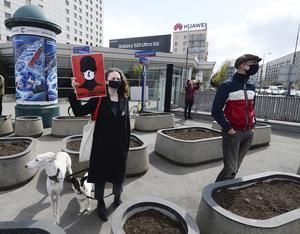En kvinna i Warszawa protesterar mot de två nya lagförslagen som ska debatteras och röstas om i veckan under en promenad med sina hundar.