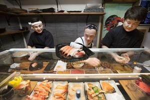 Batjargal Dashnyam fyller lådor med sushi tillsammans med Eegii och Bilgee. Batjargal ansvarar för Gävlerestaurangen och de andra två ägarna jobbar oftast i restaurangen på Kungsholmen i Stockholm.