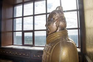 I festsalen vaktar en guldmålad terrakottasoldat i full storlek och vaktar.
