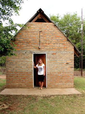 Sara i dörröppningen till sitt lilla hus i volontärbyn i Livingstone i Zambia.