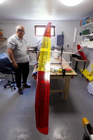Bo Svensson visar ett segelflygplan. Det är långt mellan vingspetsarna.