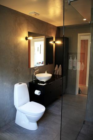 Badrummet efter är modernt i grått, vitt och svart.