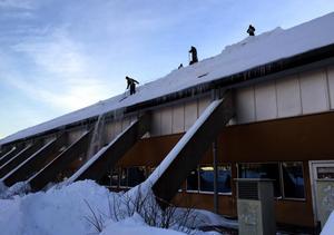 På sporthallstaket jobbar snöskottarna.