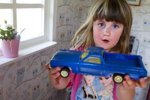 Alma Ketola visar upp en stor blå bil.