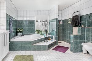 Stort badrum med nedsänkt badkar. Foto: Fastighetsbyrån Sala