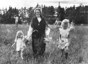 På Jamtli var det festligt värre under midsommarfirandet 1973. Här är Eva, Ann-Marie och Helene Frisk på väg till midsommarstången för att hjälpa till att klä den. Foto: Sten Eklund.