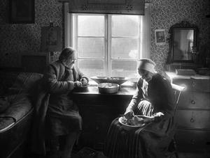Sömskar Lars Larsson och Margareta Olsdotter gifte sig 1849. Här sitter de 1906 på gården i Tibble och skalar potatis till tunnbrödbaket.Foto: Gerda Söderlund. Leksands lokalhistoriska arkiv.