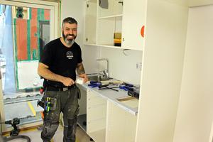 Att vara byggnadsarbetare inomhus och kunna jobba i t-shirt året runt är en av fördelarna med modulsystemet. Ett annat att man minskar risken för att bygga in fukt i konstruktionen.  Tawfik Al Amir monterar kök.