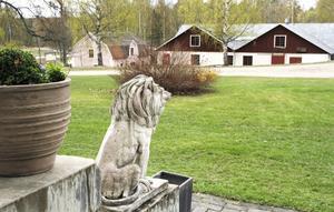Två pampiga lejon sitter på varsin sida av trappan vid huvudentrén till herrgården.