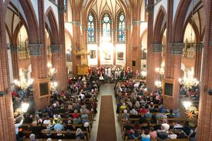 Den fullsatta Gustav Adolfs-kyrkan väntar spänt på att kören ska ta ton.