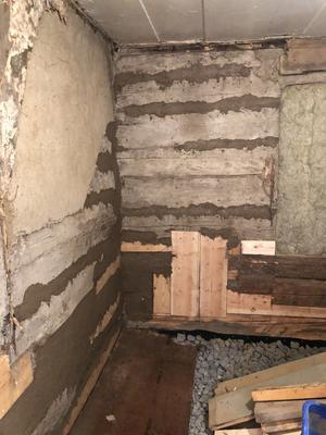 Lerklining läggs i alla sprickor och hål mellan stockarna för att fylla ut och täta. Uppe till vänster på väggen syns den gamla lerkliningen som var i bra skick och satt ordentligt fast och därmed fick vara kvar. Under golvet används en ny isoleringsmetod med returglas i form av hårt skum.