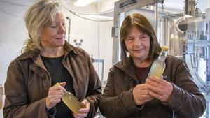 Projektledare Ylva Belin, till höger, studerar  must som just buteljerats på Köpings Musteri. Lena Ryberg-Ericsson förklarar innehållet och filosofin bakom musteriets stora utbud av olika smaker.