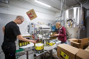Björn Appell och Nils Granberg etiketterar en batch av ölet Berliner Weisse.