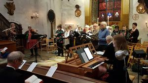 Körledaren Helene Larsson sittande vid orgeln och Torsångs kyrkokör i bakgrunden.  Foto: Lena Gäfvert