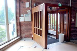 Trä möter tegel. Entrén är placerad som en sned kur in i rummet.